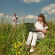 Happy Young Woman on the grass field with a laptop against the b — Stock Photo #4709087