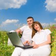 Young couple sitting on the grass field with a laptop. Against t - Stock Photo