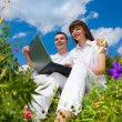 Young couple sitting on grass field with laptop — Stock Photo #4709116