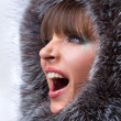 Portrait of the beautiful, shouting young woman with a fur hood — Stock Photo