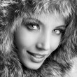 Stock Photo: Smiling young woman with a fur hood