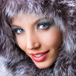 Stock Photo: Smiling young womwith fur hood