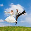 Groom and bride jumping against backdrop a sky and trees. In all — Stock Photo #4709202