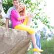 Casual happy couple sits on a rock — Stock Photo #4709253