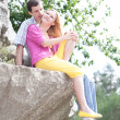 Royalty-Free Stock Photo: Casual happy couple sits on a rock