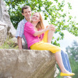 Casual happy couple sits on a rock - Foto Stock