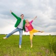 Happy smiling couple jumping in the field — Stock Photo #4709259