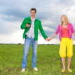Couple stay in the field. Man with mobile phone. - Stock Photo