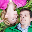Stockfoto: Young love couple lay on the green grass outdoors.