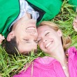 Young love couple lay on the green grass outdoors. — Stock Photo #4709298