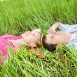 Young love couple lay on the green grass outdoors — Stockfoto
