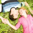 Young love couple lay on green grass outdoors — Stock Photo