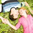 Young love couple lay on green grass outdoors — Stock Photo #4709337