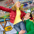 Stock Photo: Happy smiling love couple fly backdrop of graphite wall