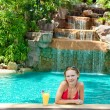 Happy young woman with an exotic cocktail in the pool — Stock Photo #4709379