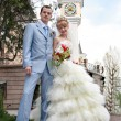 Bride and groom standing on porch looking at viewer and smiling. - Stock Photo