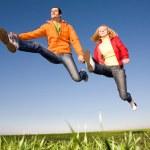 feliz pareja sonriente saltando en el cielo azul — Foto de Stock