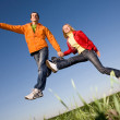 Happy smiling couple jumping in blue sky — Stock Photo