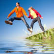 Happy smiling couple jumping in sky above a green meadow. Refle — Stock Photo #4709423