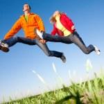 feliz pareja sonriente saltando en el cielo sobre un verde prado — Foto de Stock