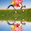 Happy young couple jumping in sky above a green meadow.Reflecte — Stock Photo #4709559