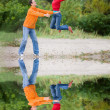 Happy Young Couple - jumping against a green tree — Stock Photo