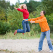 Happy Young Couple - jumping against a green tree — Stock Photo #4709649