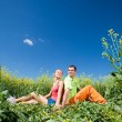 Young love Couple having fun in the field under blue sky - Stock Photo