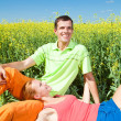 Young love couple relaxing while lying on grass - Stock Photo