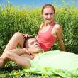 Young love couple relaxing while lying on grass — Stock Photo