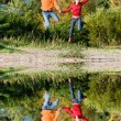 Stock Photo: Happy Young Couple - jumping in the sky against a orange-green t
