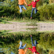 Happy Young Couple - jumping in the sky against a orange-green t — Stock Photo