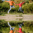Happy Young Couple - jumping in the sky against a green tree — Stock Photo