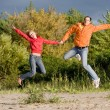 Happy Young Couple - jumping in the sky against a green tree — ストック写真