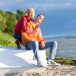 Stock Photo: Young love Couple sit on boat on bank of river
