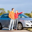 Happy young couple with their new car. Woman show something by h - Stock Photo