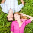 Stock Photo: Young love couple lay on the green grass outdoors.