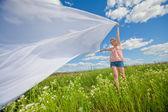 Pretty girl having fun flying in blue sky — Stock Photo
