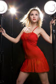 The beautiful girl in a red dress keeps hands for shone lamps — Stock Photo