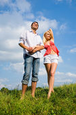 Young couple standing on summer meadow — Stock Photo