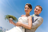 Portrait smiling groom and bride against blue sky — Stock Photo