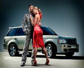 Young beautiful couple backdrop car — Foto Stock