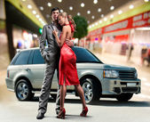Portrait Young love Couple smiling under Offroad luxury car, int — Photo
