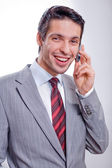 Handsome businessman speaks by a mobile phone — Stock Photo