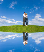 Happy young couple looking at something above a green meadow — Стоковое фото