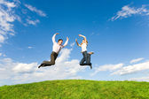 Happy Young Couple - team is jumping in the sky above a green me — Stock Photo