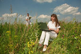 Happy Young Woman on the grass field with a laptop against the b — Foto Stock