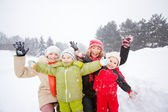 Portrait of happy mother and children together in snow on a cold — Foto Stock