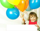 Little girl in red with balloons business card in his hand — Stock Photo