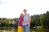 Young happy couple against a lake — Stock Photo